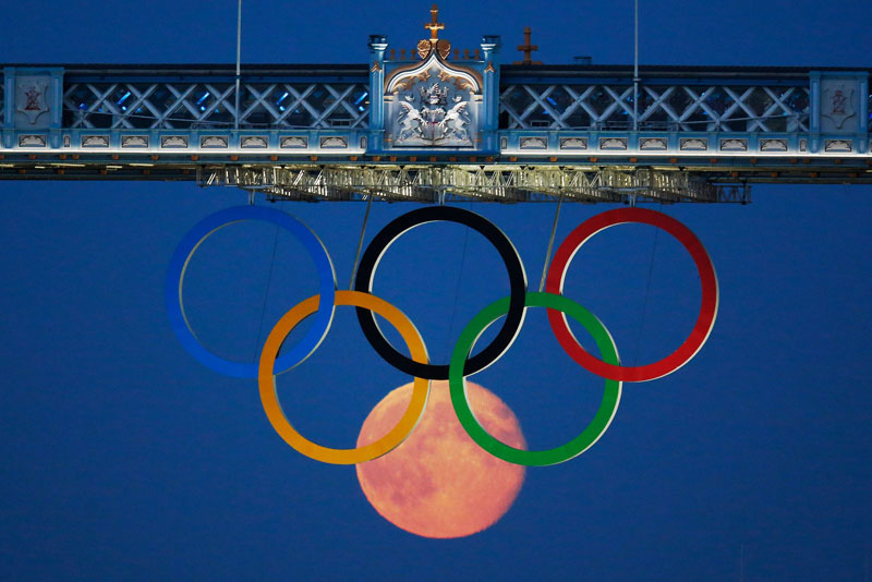 The full moon rises through the Olympic Rings hanging beneath Tower Bridge during the London 2012 Olympic Games August 3, 2012