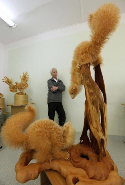 Bobkov, looks at his sculptures of life-sized birds and two martens made from cutting chips from Siberian cedar at an exhibition of his works in Kozhany