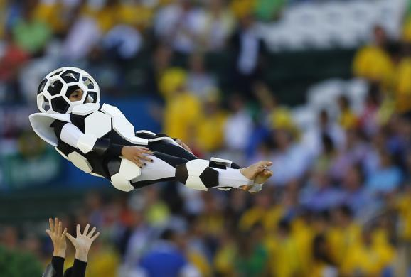 A performer is thrown into the air during the 2014 World Cup opening ceremony at the Corinthians arena in Sao Paulo