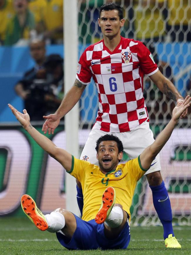 Brazil's Fred raises his arms after a penalty was called against Croatia's Dejan Lovren