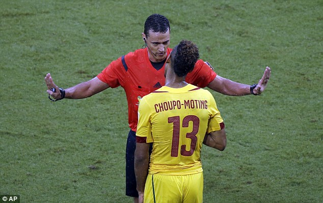 Match referee Wilmar Roldan has a word with Cameroon's Maxim Choup-Moting