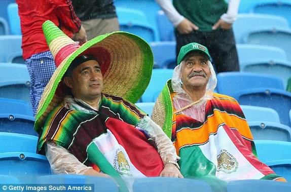 Mexico fans look on in the pouring rain in Natal