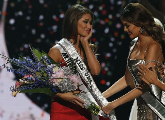 Miss Universe 2013 Gabriela Isler places the sash over Miss Nevada Nia Sanchez after she won the 2014 Miss USA beauty pageant in Baton Rouge, Louisiana