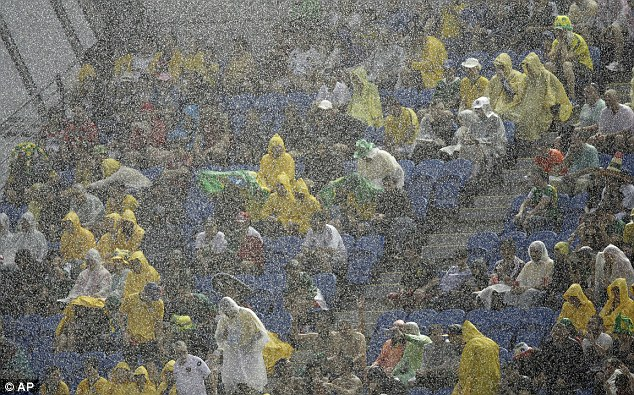Spectators sit under pouring rain as they watch the Group A match