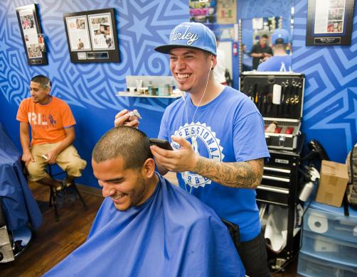 Ferrel cuts the likeness of Messi on the head of a customer at his barbershop in San Antonio