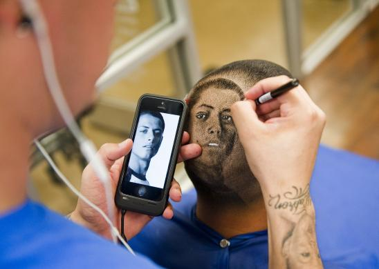 Ferrel cuts the likeness of Chicharito on the head of customer Carlos at his barbershop in San Antonio, Texas
