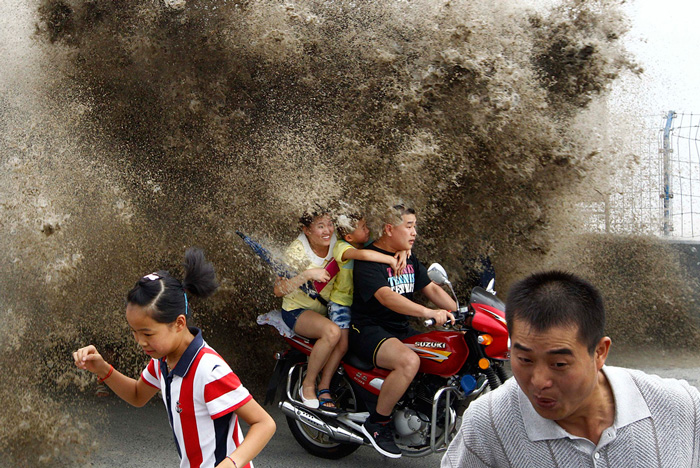 Visitors run away as waves caused by a tidal bore surge past a barrier