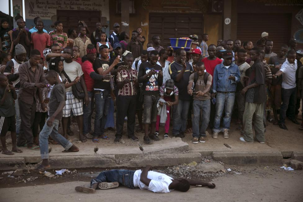 Bystanders stand around the body of a suspected Ebola victim lying in a street in the town of Koidu