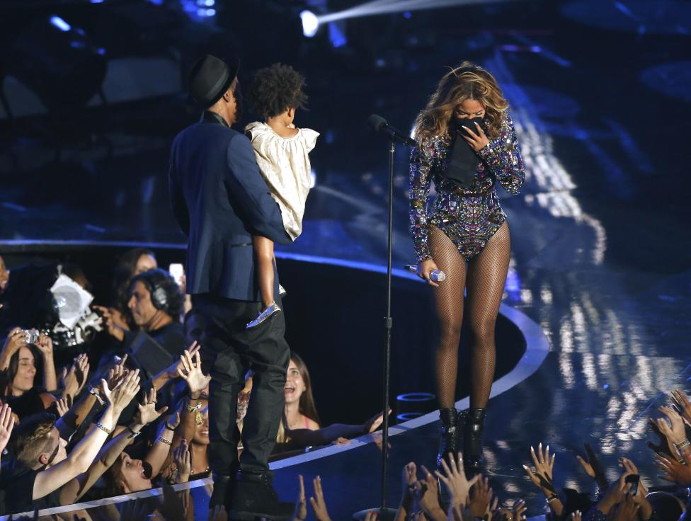 Beyonce reacts as her husband Jay-Z carries their daughter Blue Ivy onstage to present the Video Vanguard Award during the 2014 MTV Video Music Awards in Inglewood