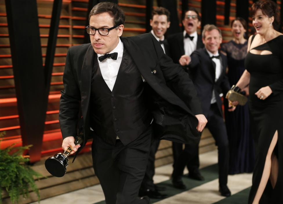Director Russell runs away with director Jonze's Oscar as they joke on the carpet at the 2014 Vanity Fair Oscars Party in West Hollywood