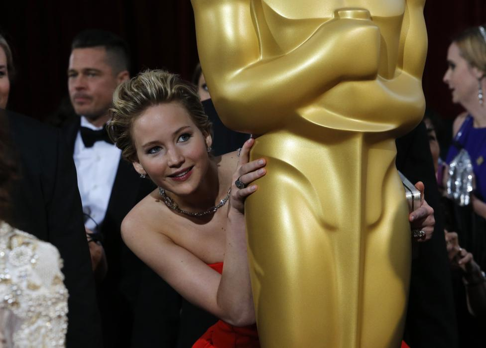"Lawrence, best supporting actress nominee for her role in the film ""American Hustle"", peeks around an Oscar statue on the red carpet at the 86th Academy Awards in Hollywood"