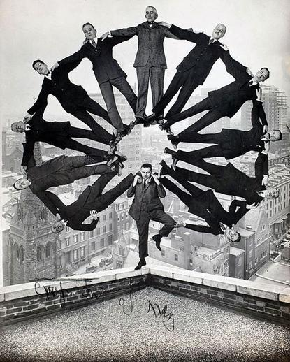 Man on Rooftop with Eleven Men in Formation on His Shoulders 1930