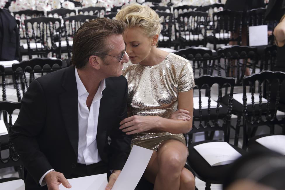 Actors Sean Penn and Charlize Theron speak together prior to the French fashion house Christian Dior Haute Couture Fall/Winter 2014-2015 fashion show by Belgian designer Raf Simons in Paris