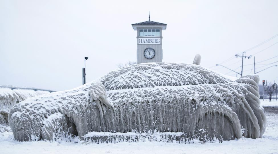 A car covered with ice remains stranded on the waterfront in Hamburg, New York
