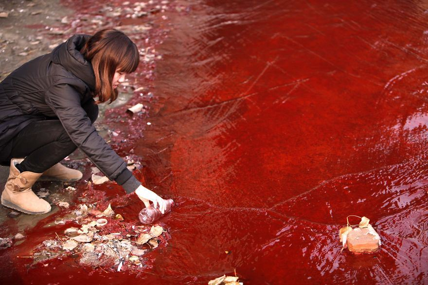 Journalist takes a sample of red polluted water from the Jianhe River