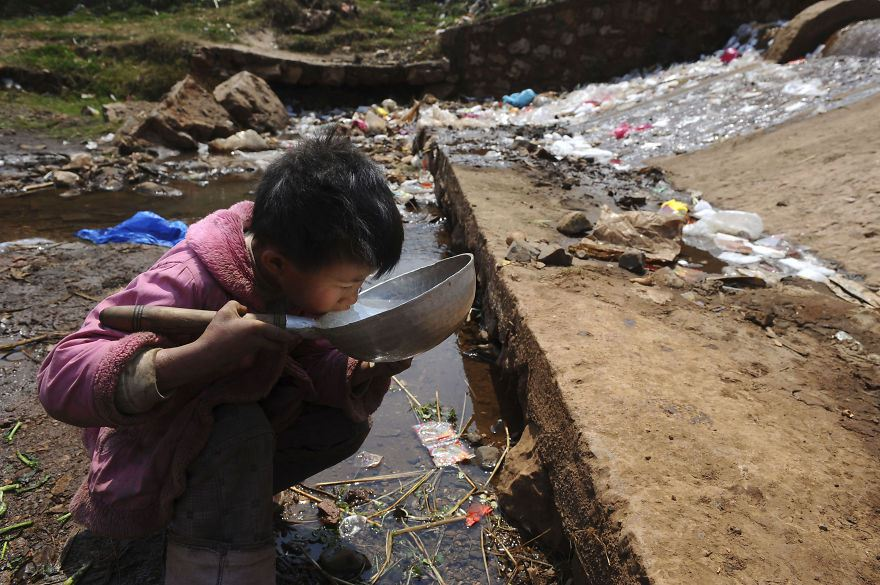 Child drinks water from stream swimming with waste in Fuyuan County, Yunnan province