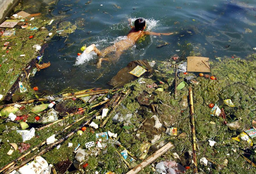 Child swims with the garbage in a polluted reservoir, Pingba