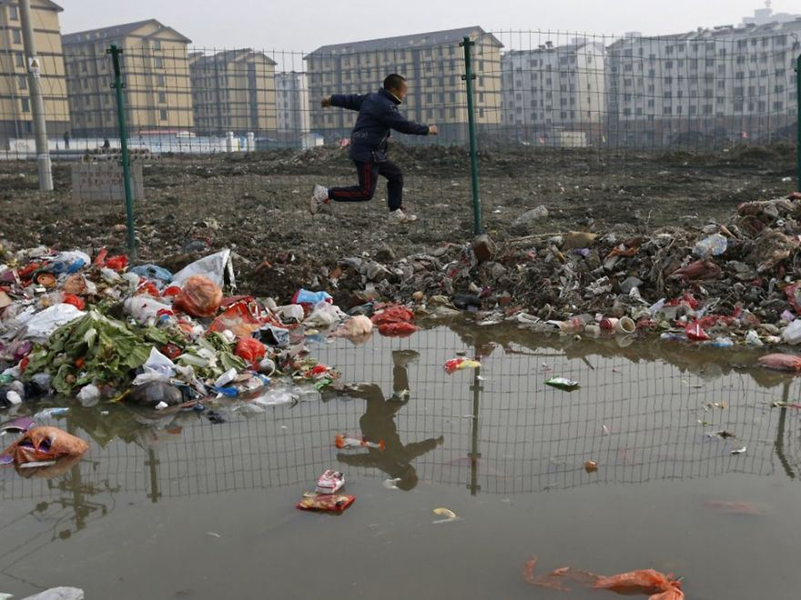 Child playing in the trash at a village, Jiaxing