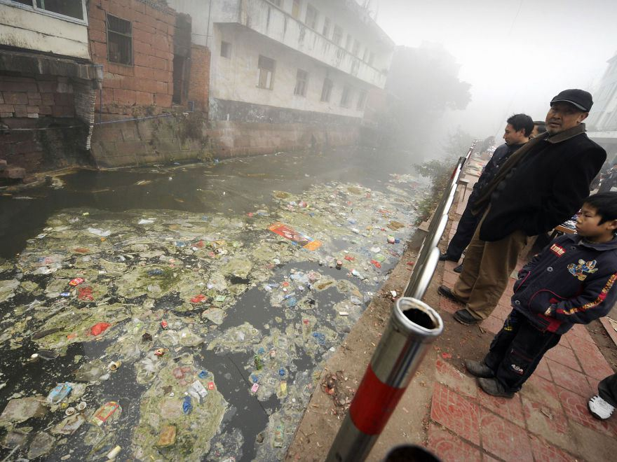 Residents stare at a heavily polluted river in Zhugao, Sichuan province