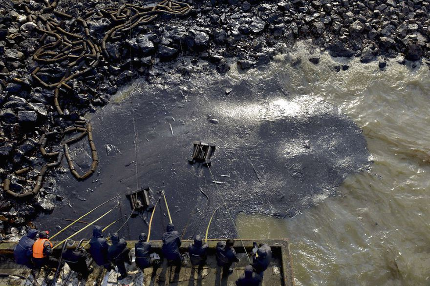 Workers clean up leaked oil after an oil pipeline explosion, Qingdao, Shandong